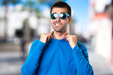 Handsome young man with sunglasses on unfocused background