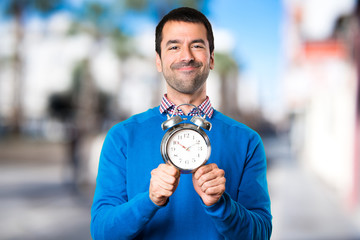 Handsome young man holding vintage clock on unfocused background