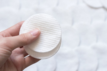 Female hand holding cotten pads. Beauty, spa, body care.
