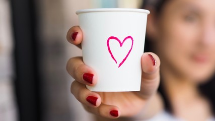 Woman holding a paper cup with heart drawing.