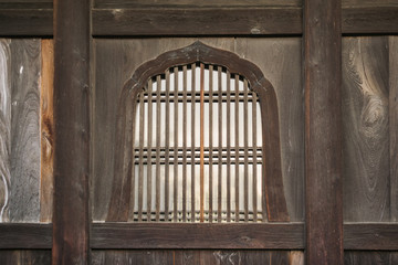 Background featuring details of Japanese traditional wooden windows with parallel and perpendicular elements in design in Kyoto, Japan.