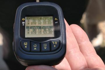 Hand hält einen GPS-Logger mit den Koordinaten der Äquator-Nulllinie in Ekuador