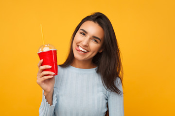 Brunette cheerful girl holding a soda cup