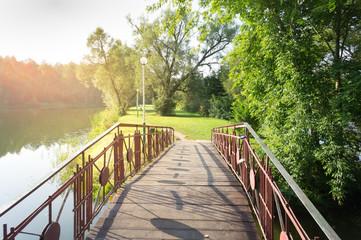 Autumn landscape. Park with lake and bridge.