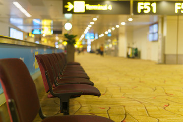 Row of empty brown chair for passenger to wait before departure time in gate F51 at the airport.