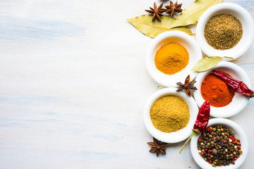 Different spices on white wooden table