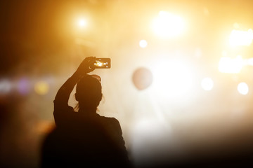 Silhouette of girl with a smartphone taking photo of concert stage.