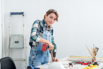 pretty young smiling woman using cordless drill