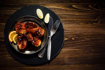 Roast chicken drumsticks on wooden background