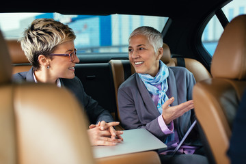Senior business woman and her assistant sitting in limousine talking and working