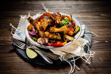 Grilled chicken legs with vegetables on wooden table background