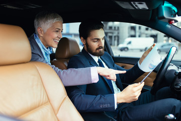 Senior business woman sitting in limousine and talking with her driver. Business concept.
