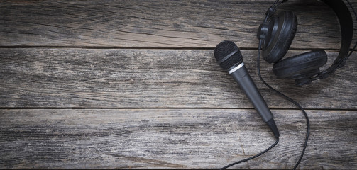 Microphone and headphone on a wooden background