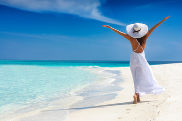 Attraktive Frau in weißem Kleid läuft an einem tropischen Strand und ist glücklich