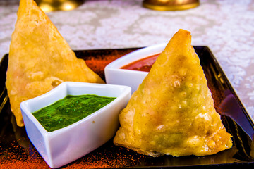 Indian samosas with sauces on black plate
