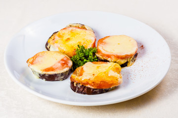 Eggplants baked with tomato and cheese on white plate