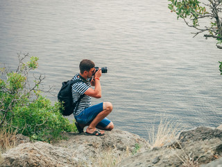 photographer tourist taking pictures sitting on the seascape