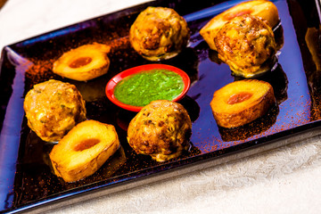 Fried meatballs with green sauce on black plate