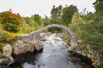 The ancient packhorse bridge at Carrbridge, in the Cairngorms National Park in Scotland in autumn