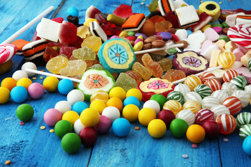 candies with jelly and sugar. colorful array of different childs sweets and treats on light blue wood background