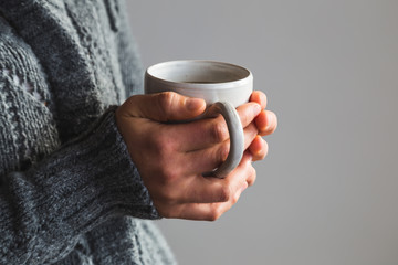 Woman in woolly gray sweater holding warm cup of tea