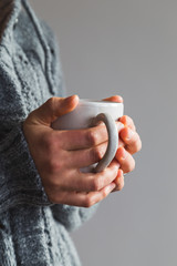 Woman wearing gray woolly cardigan holding warm cup of tea