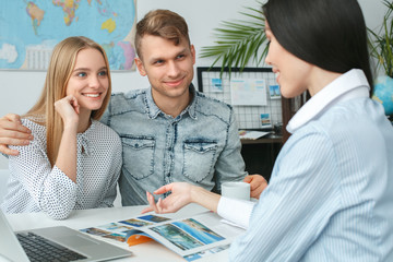 Young couple in a tour agency communication with a travel agent travelling concept tour destination