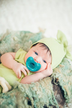 portrait of a sweet newborn in green clothes with a pacifier. the concept of childhood. looking in the camera.
