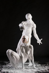 Naked couple covered by white body paint shot