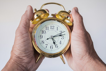 Both hands of the old man holding the alarm clock as a means to
