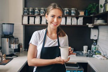 Young Caucasian barista hands holding paper cup with coffee. Small business and person at work concept