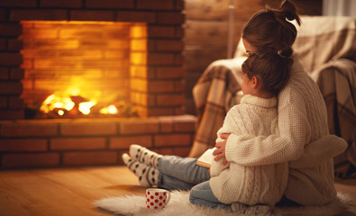 family mother and child hugs and warm on winter evening by fireplace.