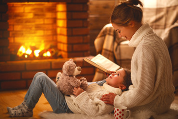 family mother and child reading book on winter evening by fireplace.