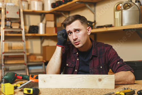 e3e951df Handsome upset sad caucasian young man in plaid shirt, black T-shirt,  gloves working in carpentry workshop at wooden table place with piece of  wood, ...