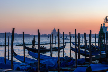 VENICE, ITALY - JANUARY 02 2018: Gondoloas  in the San Marco basin with Santissimo Redentore church and Giudecca island silhouette at sunset
