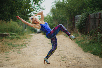 young smiling girl in colored leggings, blue top, white hat and on high heels dancing
