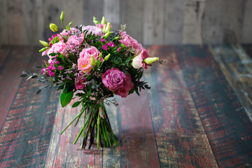 Rustic wedding bouquet with roses and Lisianthus flowers in different shades of pink. Fototapete
