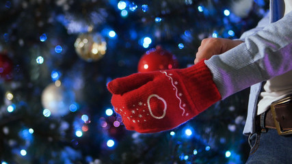Spread out hand in red woolen glove on Christmas background, concept of joy in winter time. Man wearing a Christmas mitten in the hand