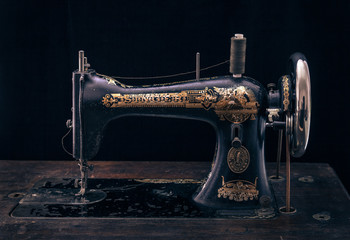 Close up of antique sewing machine on black background.