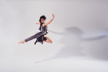 Modern teen contemporary dancer poses in front of the studio background.