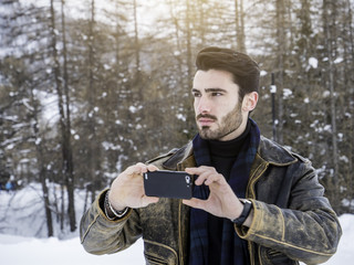 Handsome young man using smarpthone to take photographs of the landscape, while posing among snowy woods in the mountain