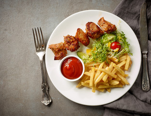 Plate of fried potatoes and pork kebab