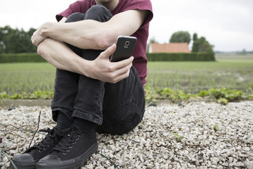An anonymous young man or boy holding his phone and looking at it. A concept about struggling with yourself, being mentally and physically tangled up, autism, online bullying and suicide thoughts.