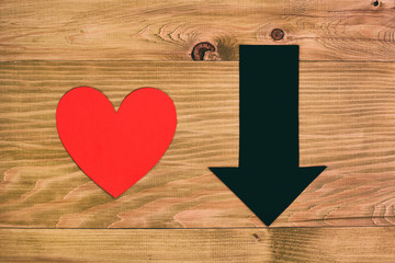 Red heart and arrow going down on wooden table,relationship breakup concept.