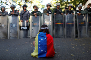 A girl wears a Venezuelan flag as Venezuelan security forces block access to opposition supporters and mourners of rogue ex-policeman Oscar Perez to the main morgue of the city, in Caracas