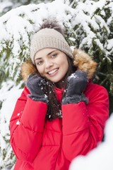 beautiful woman is happy while is snowing in the park.