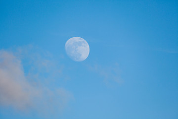 Moon behind cloud at blue day sky