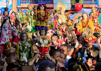 Devotees raise figurines of the Santo Nino (Holy Child Jesus) as they receive blessings with holy water from the lay minister during the annual feast day of Santo Nino in Tondo city