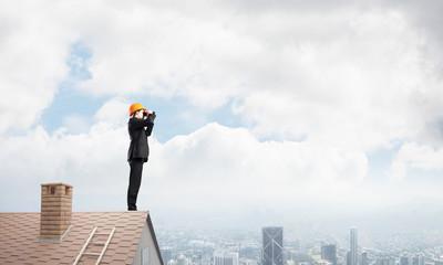 Engineer man standing on roof and looking in binoculars. Mixed media