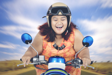 Young fat woman riding a scooter